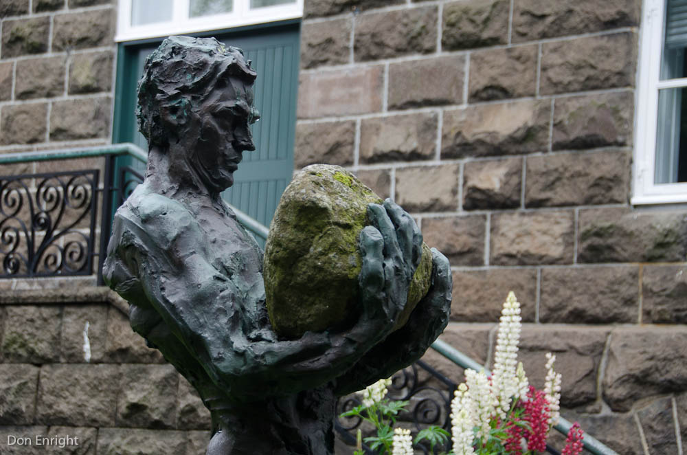 sculpture of man with rock