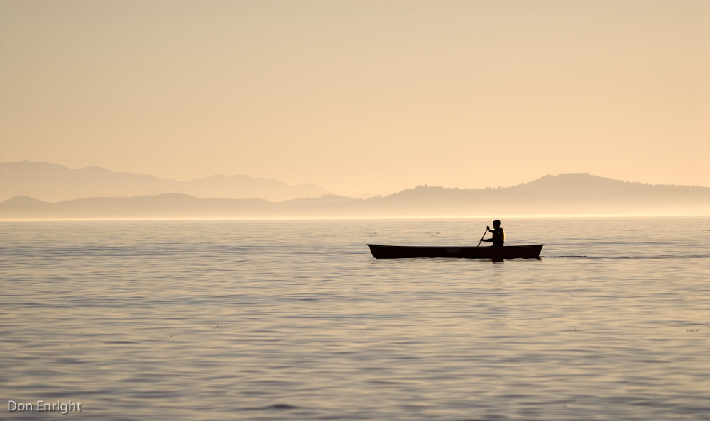 A lone canoeist paddles in the evening mist.